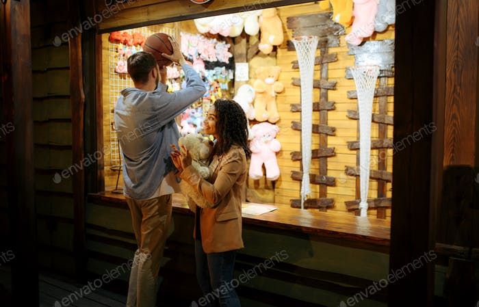 Couple play in shooting gallery, amusement park