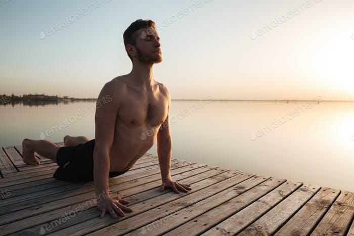 Handsome young sportsman make yoga exercises at the beach.