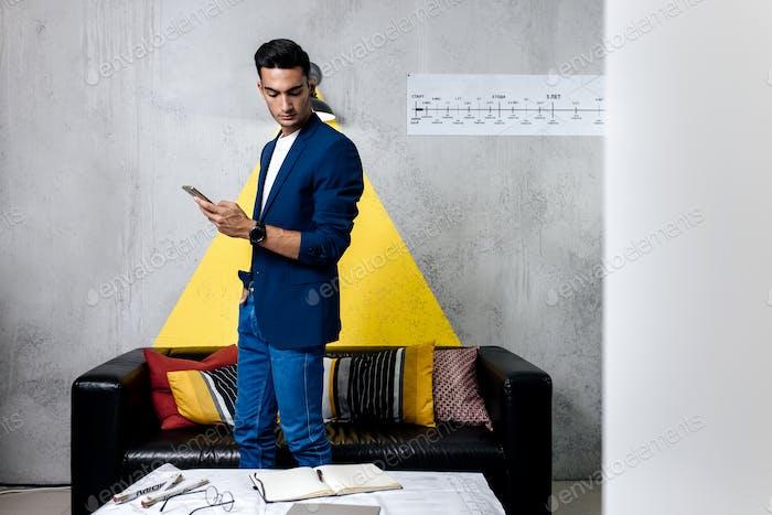 Профессиональный молодой архитектор использует телефон в комнате со стильным интерьером
