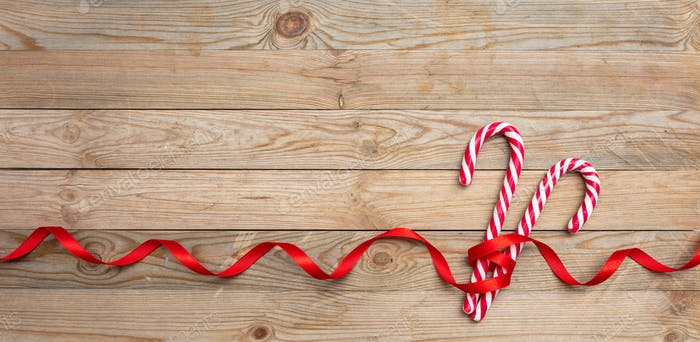 Candy canes on wooden background, copy space