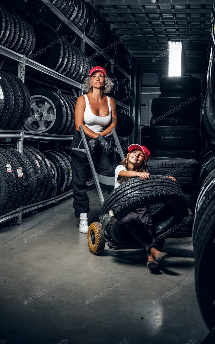 Woman is carrying tyre on the truck with girl