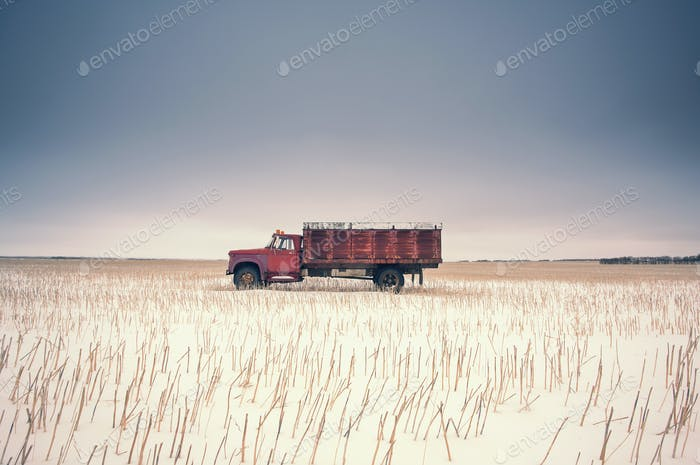 Ein Bauernhof LKW in einem Stoppelfeld umgeben von Freiraum.