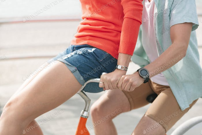 Midsection of Caucasian couple enjoying bicycle ride at beach on a sunny day