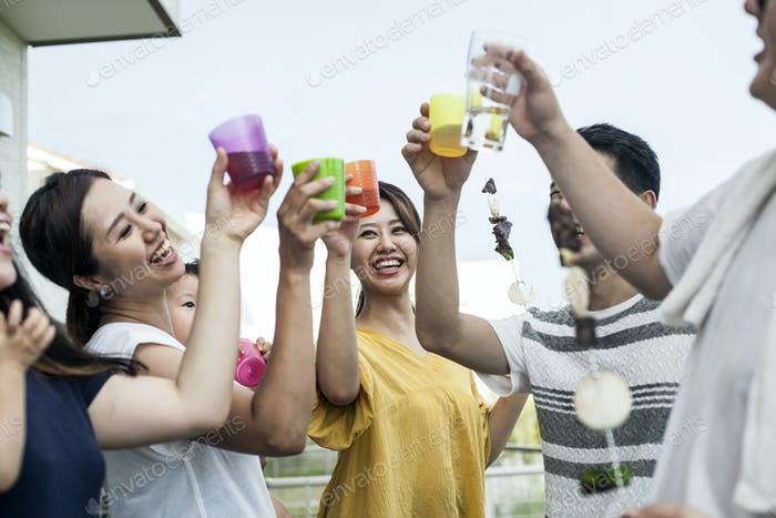 Group of cheerful young Japanese men and women standing outdoors, toasting with plastic beakers.