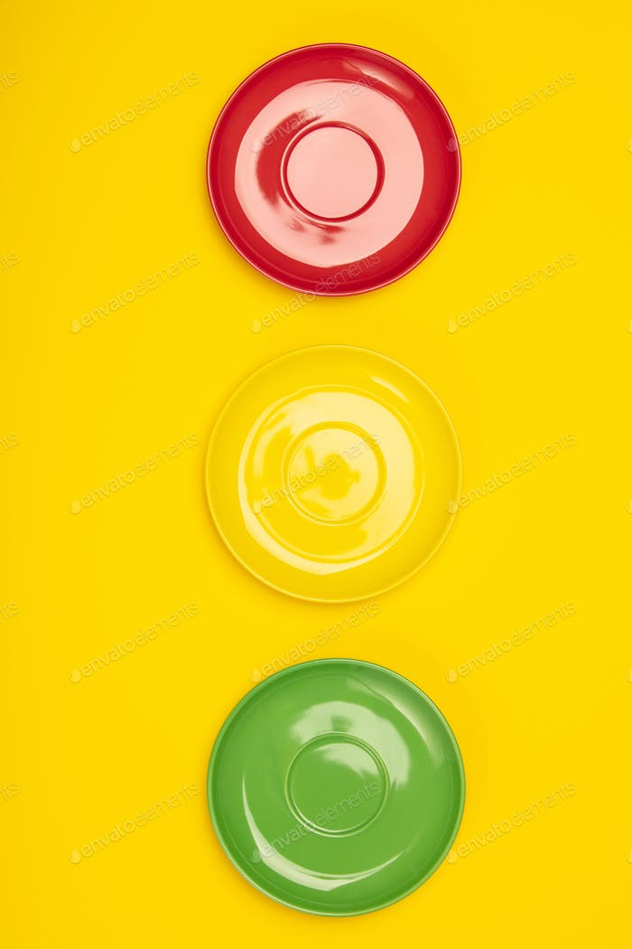 Colorful plates on yellow background, flat lay