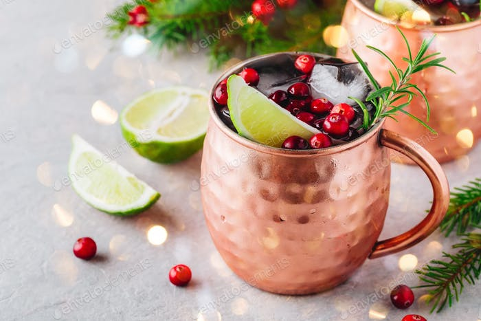 Holiday Moscow Mule ice cold Cocktail in copper cup with cranberries