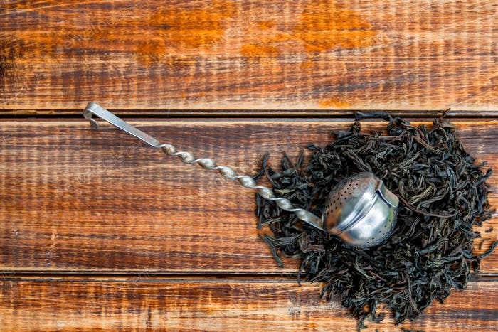 Vintage strainer with dry leaves of black tea on wooden