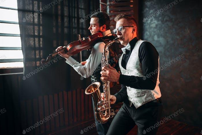 Saxo Hombre y violín dueto tocando la melodía Clásica