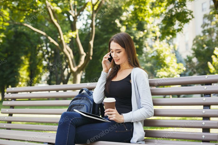 Smiling woman talking on mobile phone outdoors