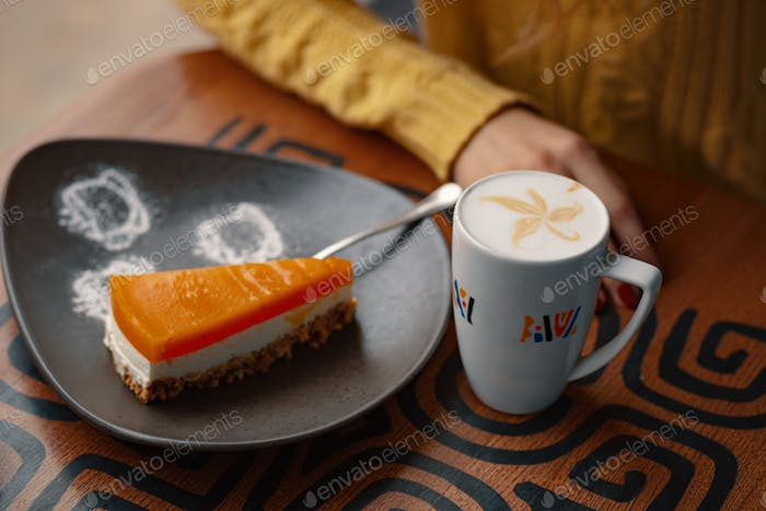 Slice of delicious carrot cheesecake and latte cup