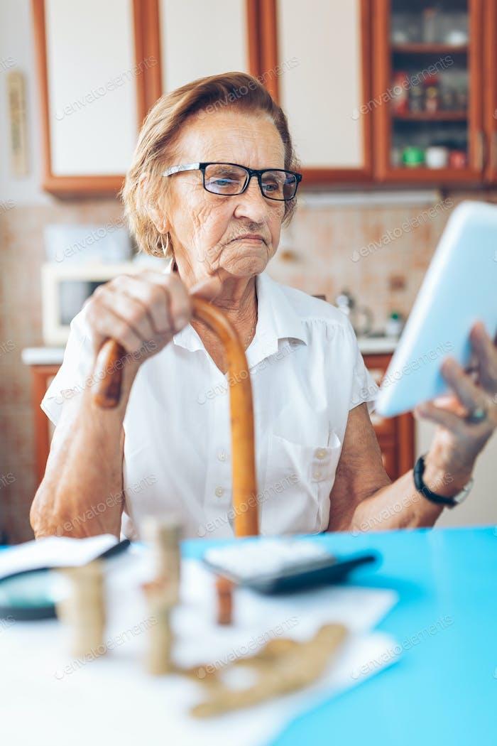 Senior Frau überprüft ihre Finanzen und Erfindungen