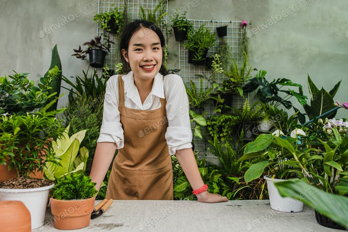 Young gardener woman stand with smile at greenhouse