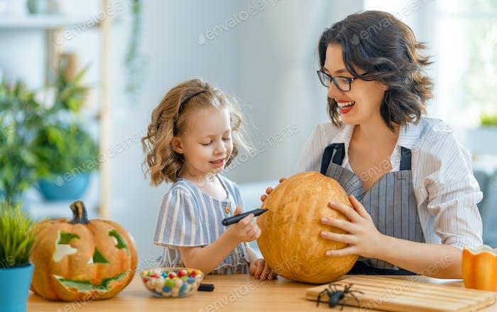 Glückliche Familie bereitet sich auf Halloween vor.