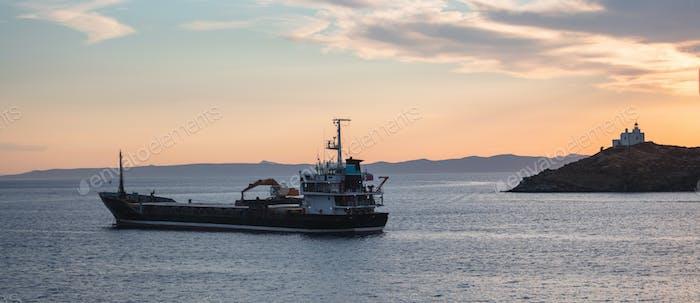 Ship on calm sea at sunset in the Aegean sea, Greece. Lighthouse on a cape at Kea island.