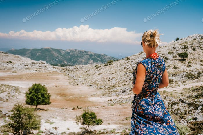 Tanned girl on Mountainscape plateau of highland countryside and beautiful nature. Rocky stones and