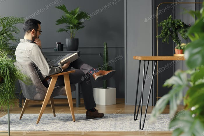 Modern man reading book while sitting in grey armchair in trendy