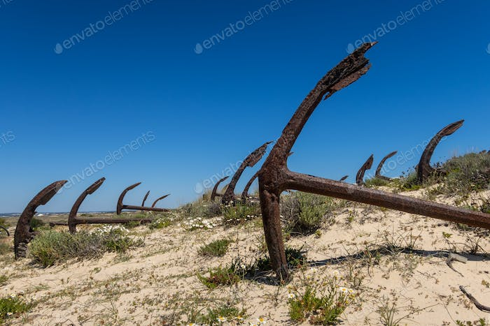 Rusting anchors buried in the sand on Praia do Barril beach