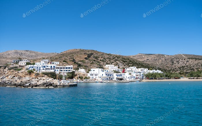 Sikinos greek island port, white buildings and blue sky background.