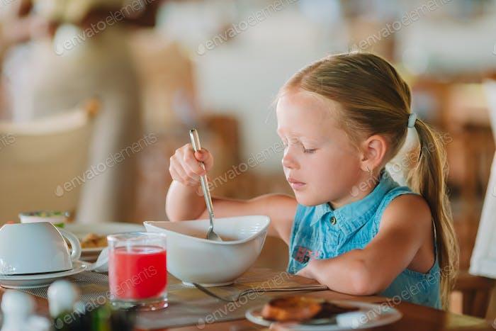 Adorable niña tener desayuno en al aire libre café