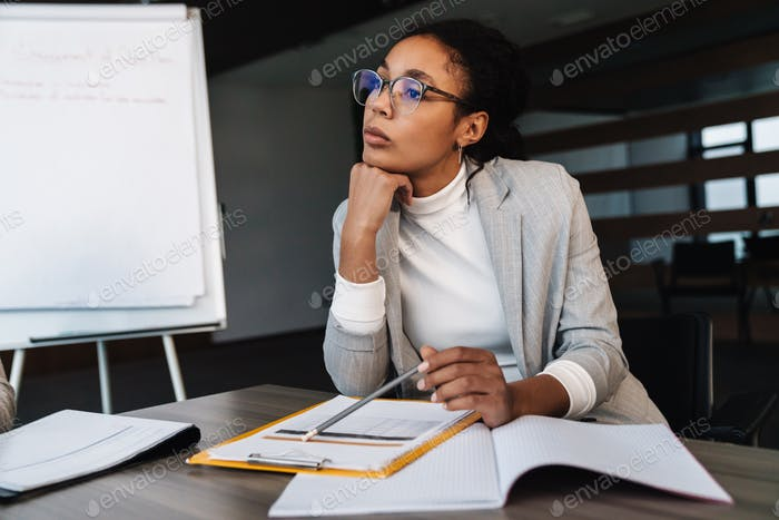 Image of african american businesswoman working with papers in office