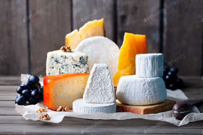Surtido de queso: queso azul, queso duro, queso blando en un papel pergamino. Fondo de madera.