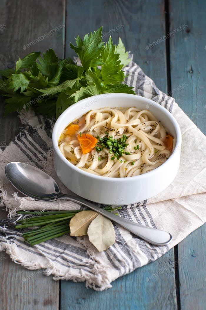 Homemade chicken soup with homemade noodles on an old wooden tab