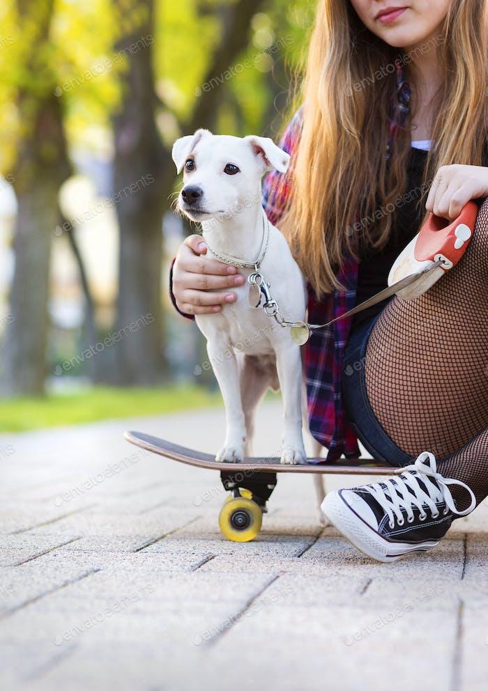 Teenage girl with skateboard and dog