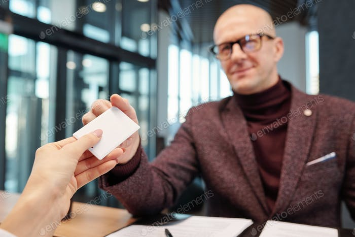 Hand of businessman taking card from empty hotel room at reception counter