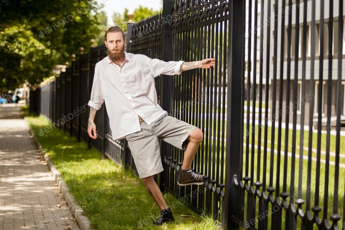 Bearded hipster posing next to a fence
