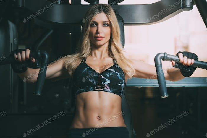 beautiful blonde woman working out in the gym chest machine