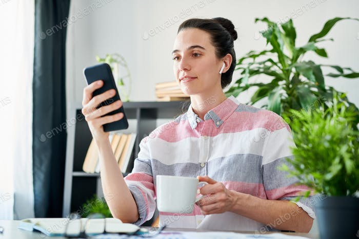 Woman Using Smartphone during Coffee Break