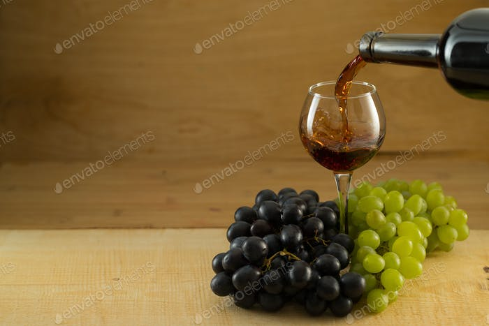 Bunches of grapes and a glass of wine on a wooden background