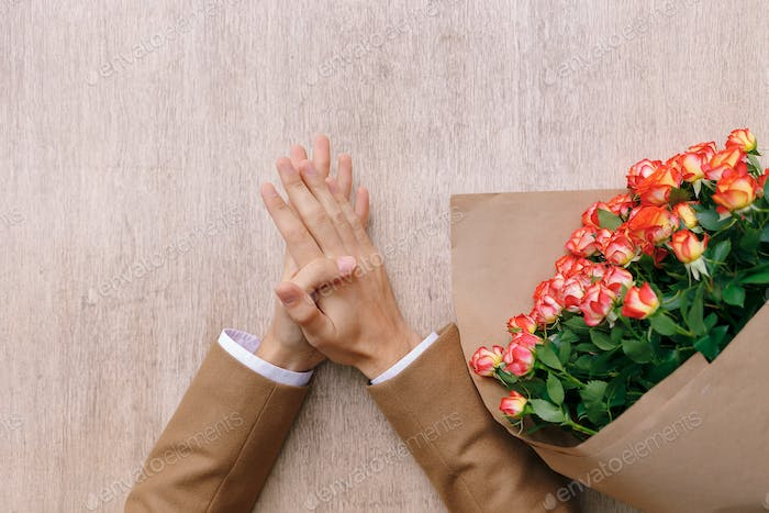 Accurate man hands with palm over palm and a bunch of roses