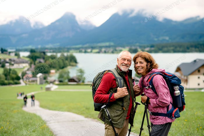 Senior pensioner couple with nordic walking poles hiking in nature.