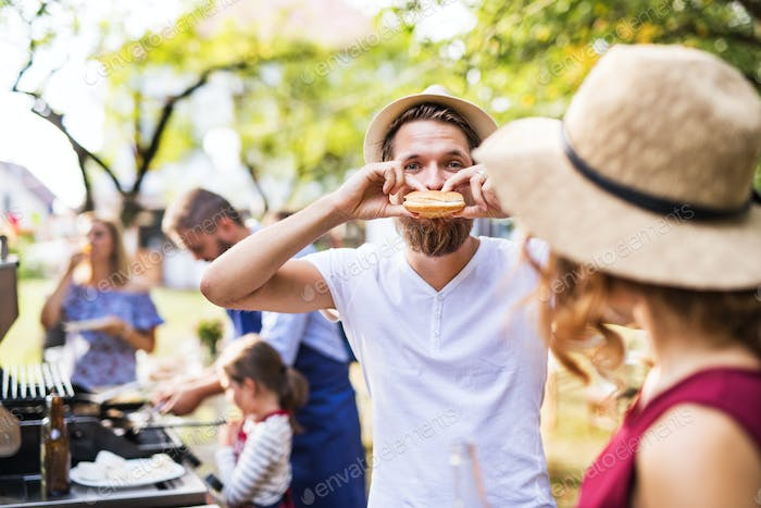 A young man eating a hamburger on a family celebration or a barbecue party outside.
