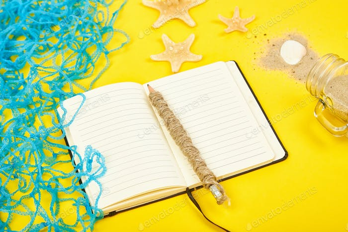 Notebook, starfishes and seashells, glass with sand