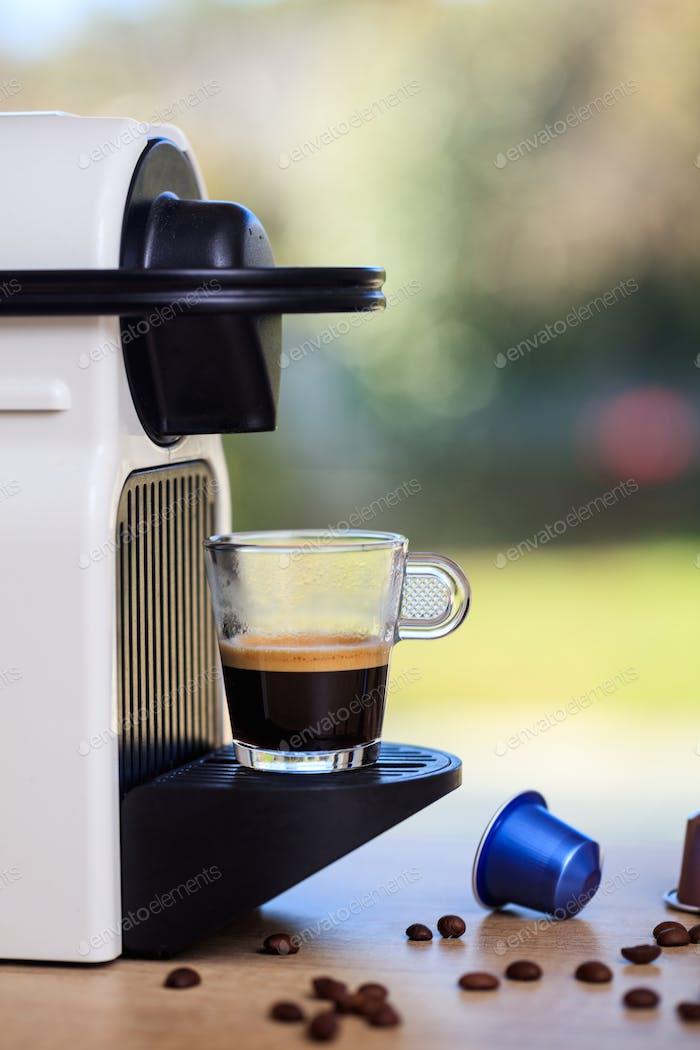Espresso-Kaffeemaschine auf einem Holztisch, unschärfer grüner Hintergrund