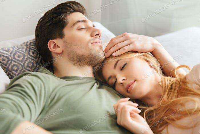 Cute young loving couple sleeping on sofa