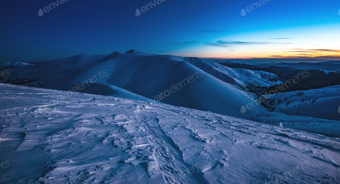 View of a steep ski slope with comfortable tracks