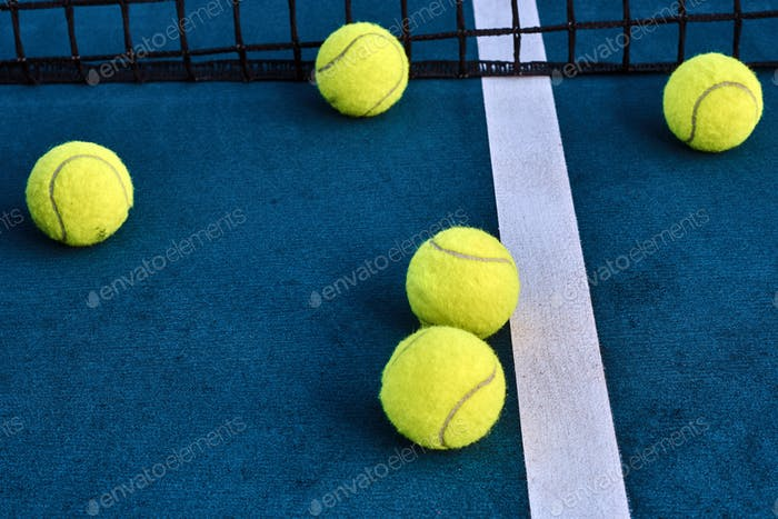 Pelotas de tenis debajo de la red en la cancha