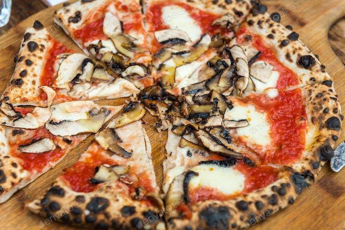 Portobello Italienische Pizza auf der dünnen Basis mit geschmolzenem Mozzarella