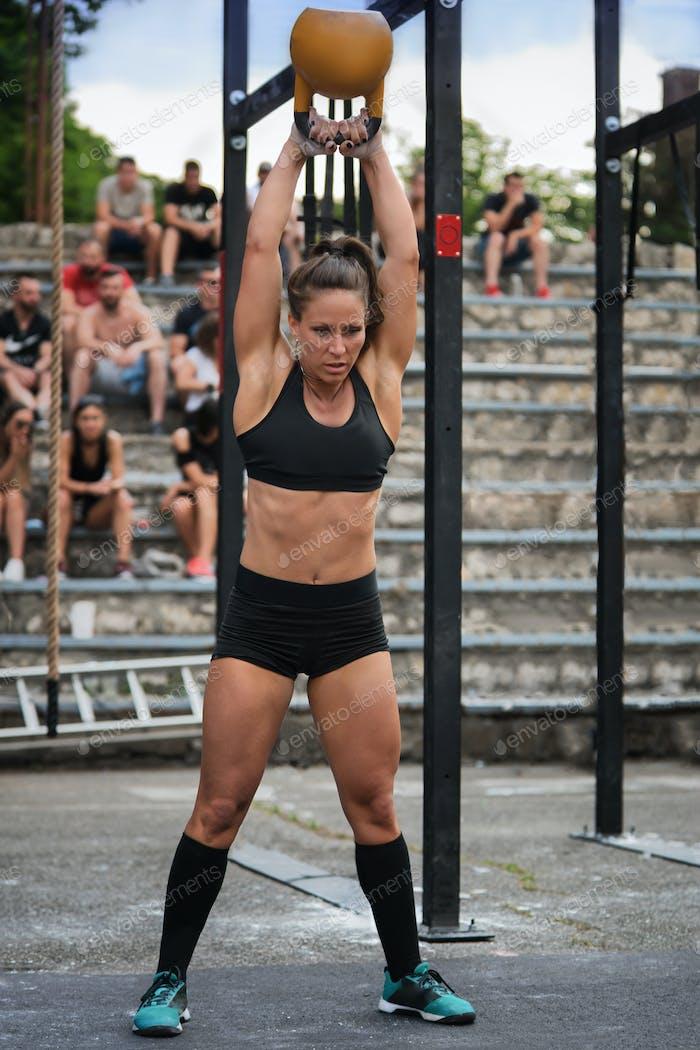 Cross training fitnes, female athlete with kettlebell