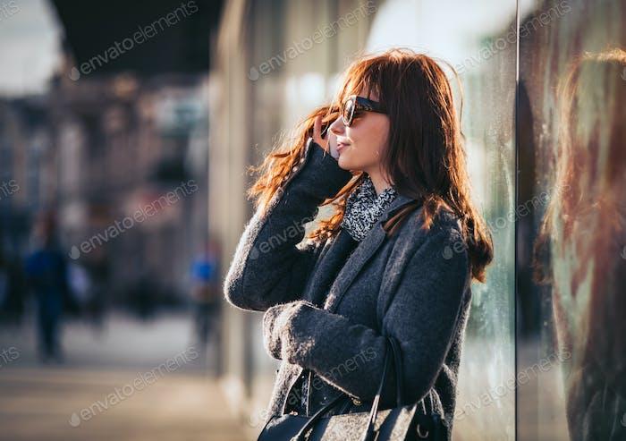 Девушка на улице с помощью мобильного телефона