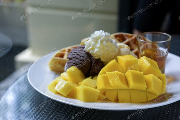 Ripe mango, ice cream, waffles and honey in white dish.