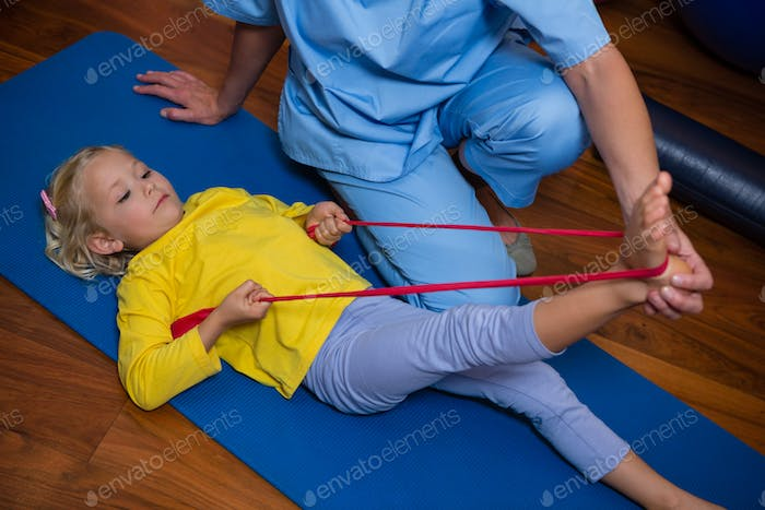 Female physiotherapist assisting a girl patient while exercising