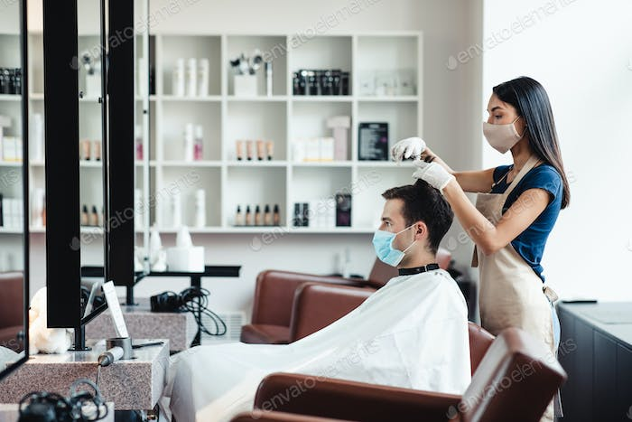 Hairdresser and client taking precautions during haircut at barber shop