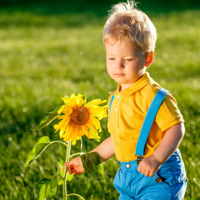 One year old baby boy looking at sunflower