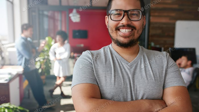 Smiling male designer looking at camera at office
