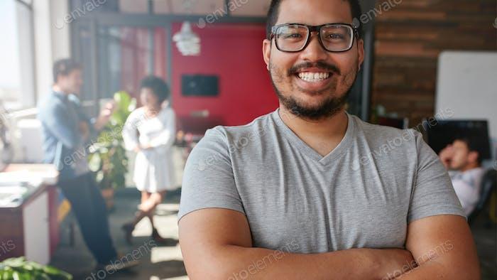 Lächelnd männlichen Designer Blick auf die Kamera im Büro