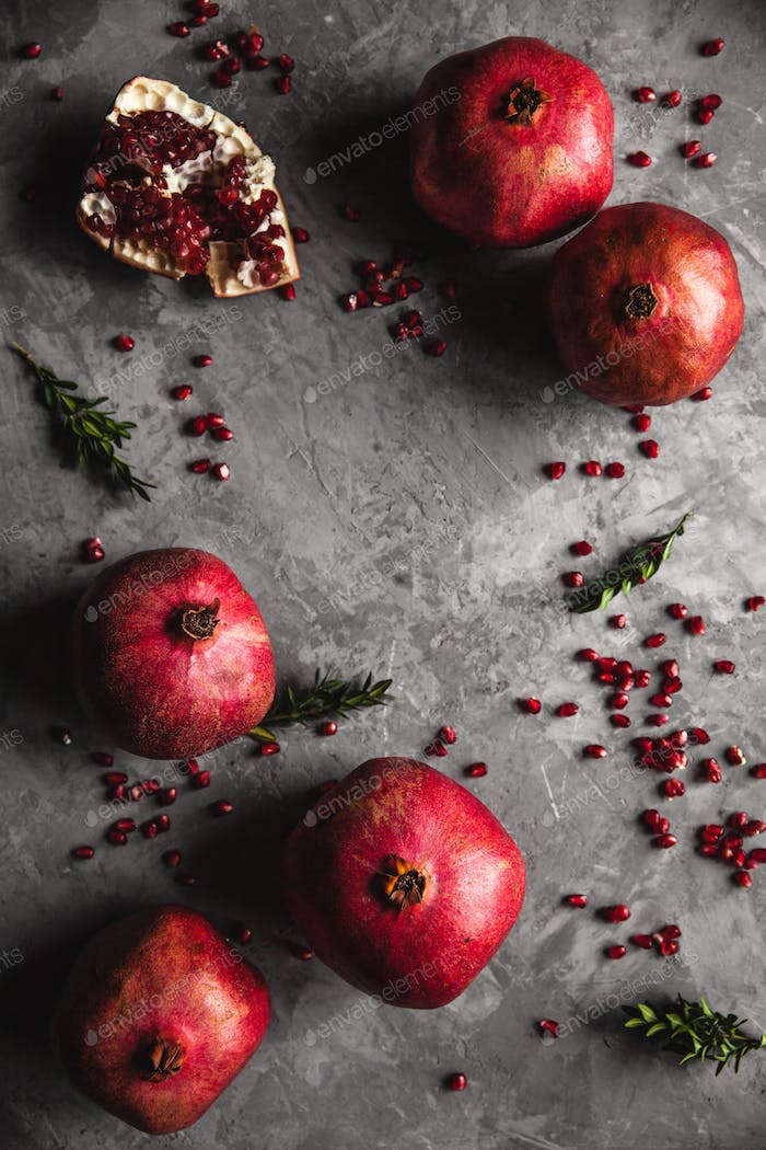 Pomegranate fruit. Ripe and juicy pomegranate on rustic grey background with copy space for text
